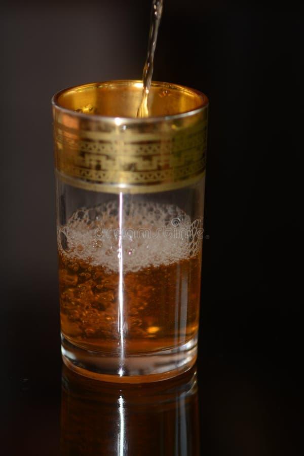 Chá marroquino derramado no vidro imagens de stock