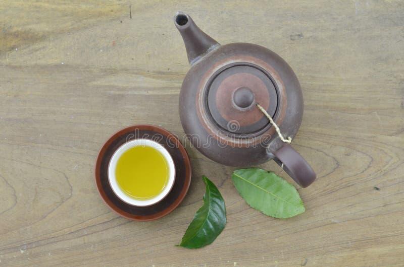 Chá no copo e no bule com chá verde fresco da folha no fundo de madeira fotos de stock royalty free