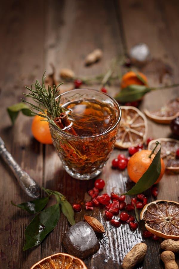 Chá perfumado do fruto com tangerinas, os limões secados e os alecrins em uma tabela de madeira Estilo country imagens de stock