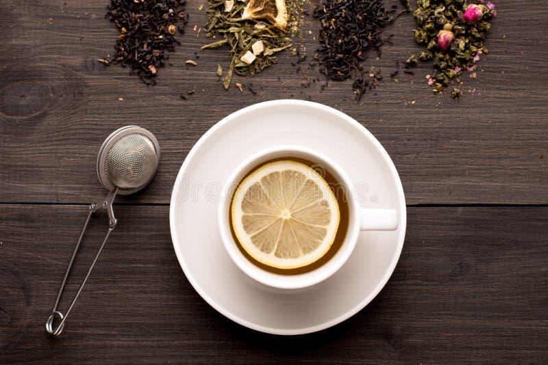 Chá preto com limão e diversas vistas do chá em um fundo de madeira foto de stock