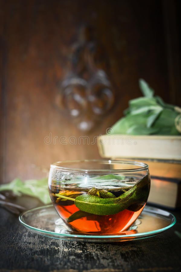Chá prudente na tabela rústica sobre livros velhos e o fundo de madeira foto de stock