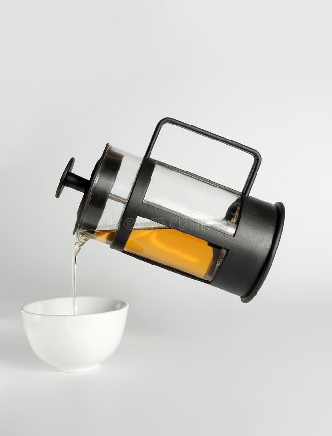 Chá que derrama da imprensa francesa em um copo branco imagens de stock
