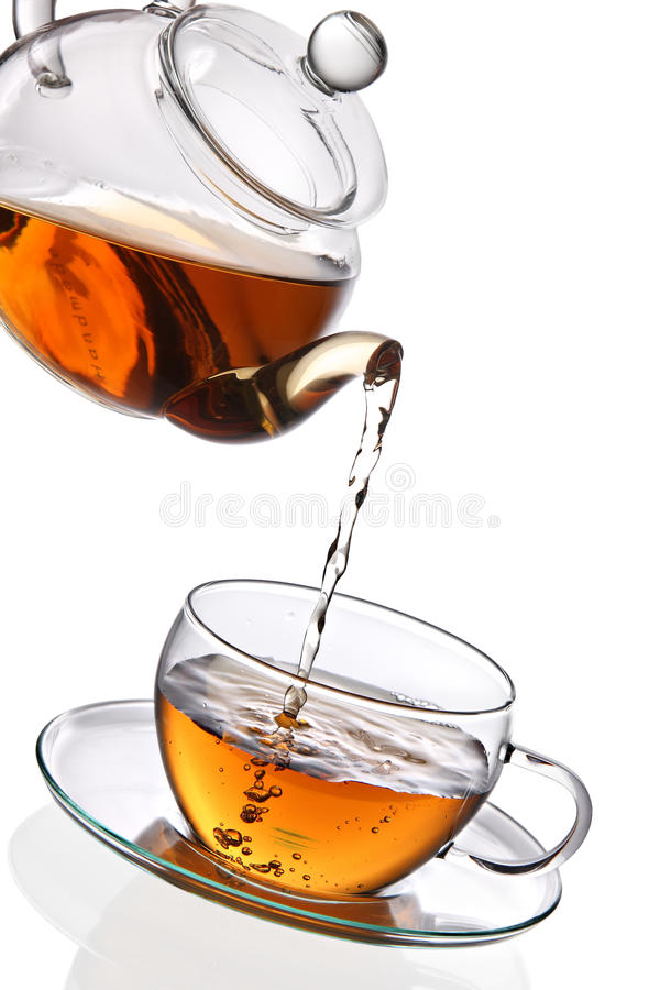Chá que está sendo derramado no copo de chá de vidro fotos de stock