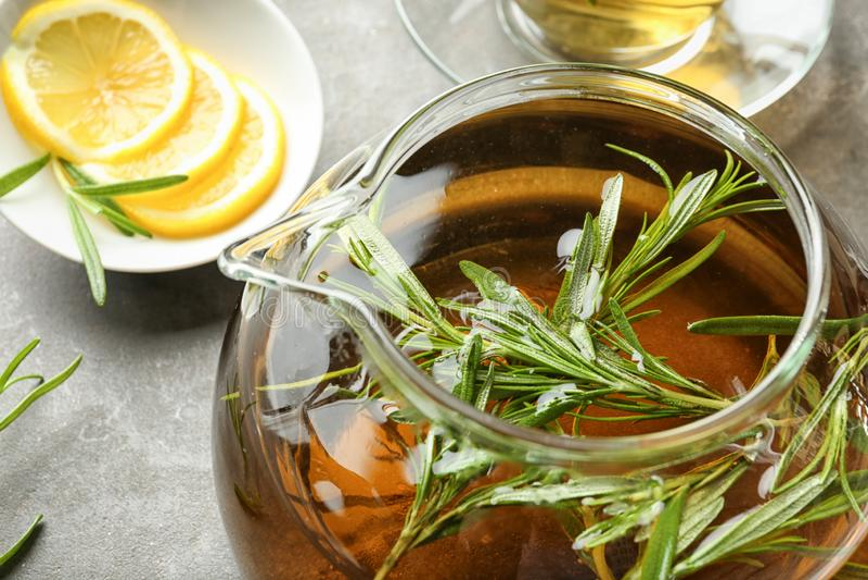 Chá quente com alecrins frescos no bule de vidro na tabela cinzenta foto de stock royalty free