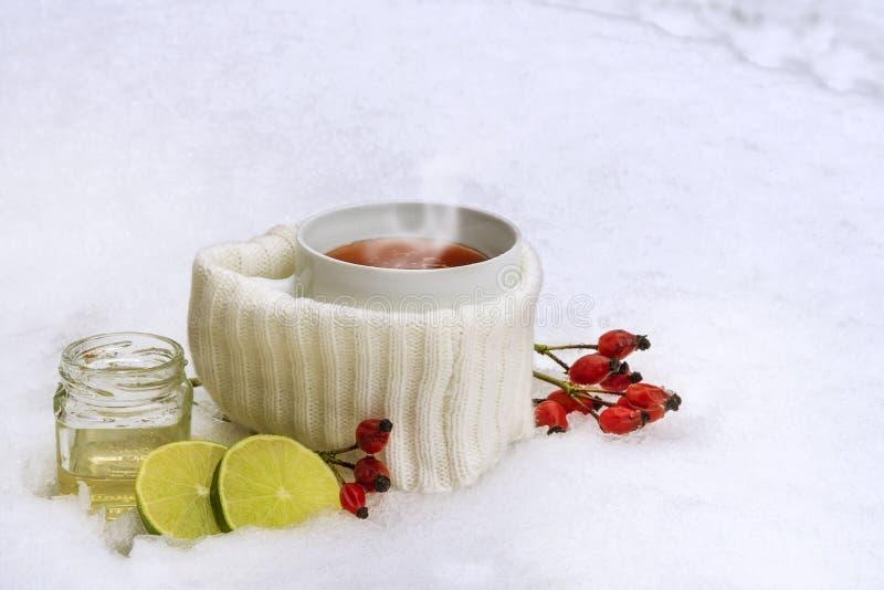 Chá quente dos quadris cor-de-rosa vermelhos com limão e mel na neve, bebida da vitamina do inverno contra fotografia de stock
