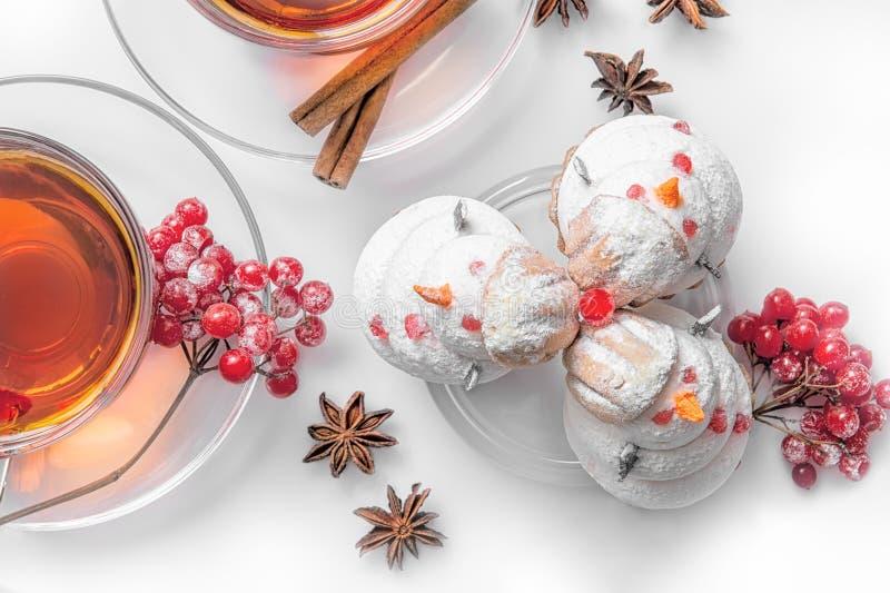 Chá quente no Natal no copo transparente de vidro com árvore do chá e nos bolos na forma dos bonecos de neve fora da merengue, ca imagem de stock