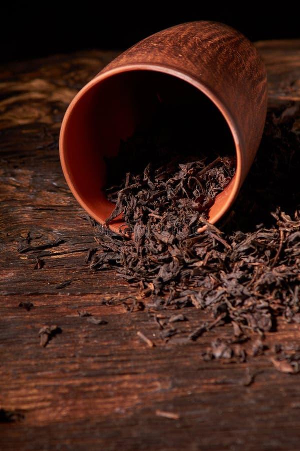 Chá seco no copo da argila na tabela de madeira Foco seletivo, fim acima imagem de stock royalty free