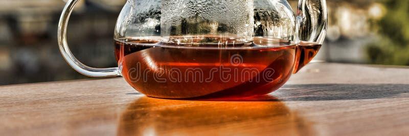 Chá Teapot com chá Chá do café da manhã em um bule de vidro no fundo da cidade moderna Adultos novos fotos de stock