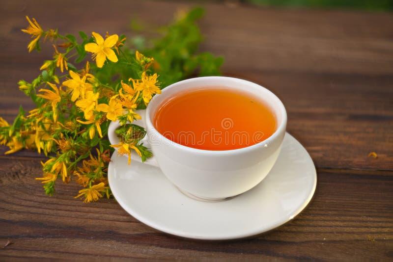 Chá tutsan delicioso em uma bacia de vidro bonita na tabela fotos de stock