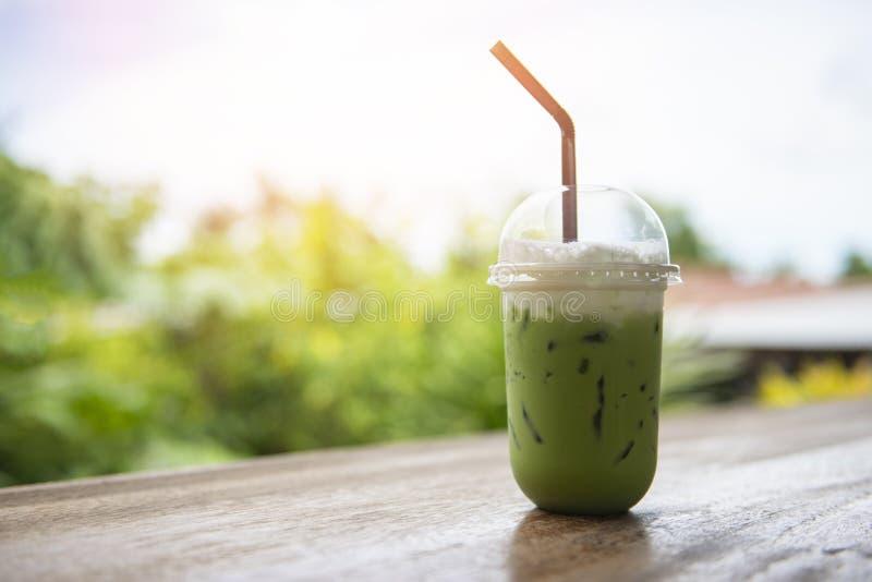 Chá verde congelado no frappe plástico do latte do chá verde do copo/matcha e palha na tabela de madeira com natureza foto de stock royalty free