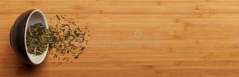 Chá verde derramado do kukicha japonês do copo sobre a placa de bambu imagem de stock