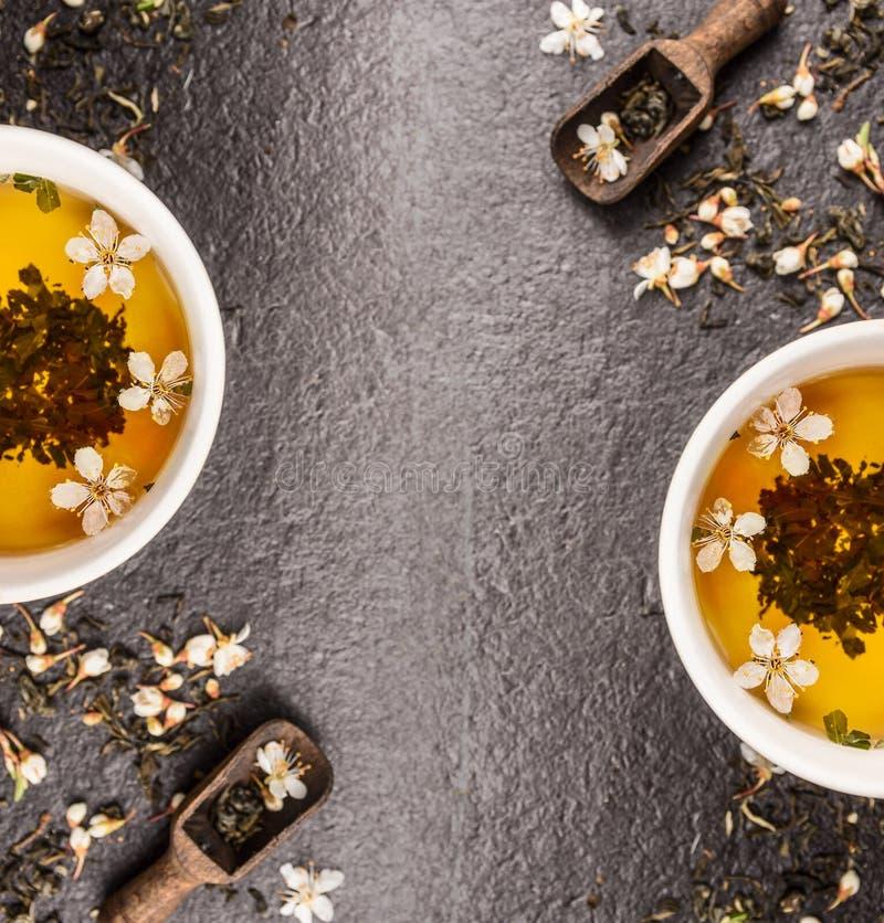 Chá verde do jasmim com flores frescas e copos de chá no fundo de pedra preto, quadro, vista superior fotografia de stock