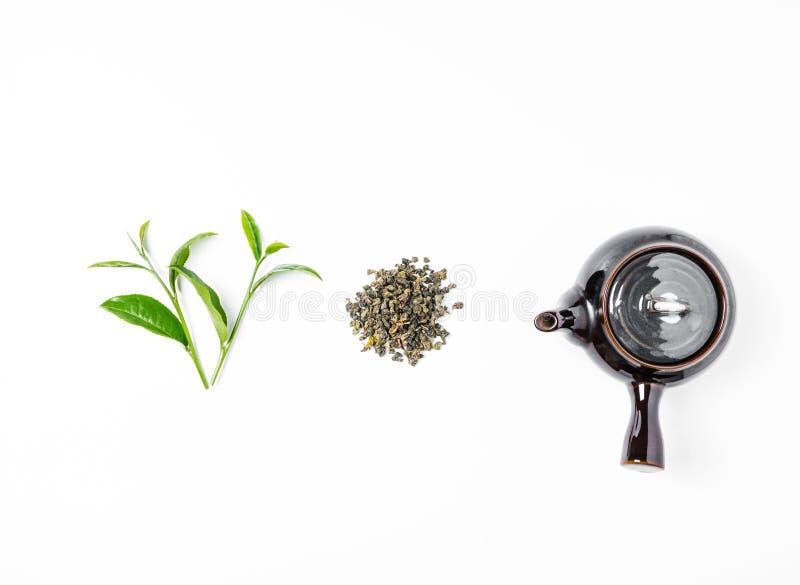 Chá verde no potenciômetro do chá no fundo branco imagens de stock royalty free