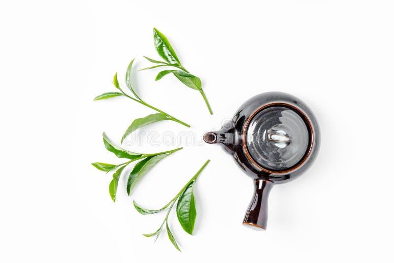 Chá verde no potenciômetro do chá no fundo branco imagens de stock