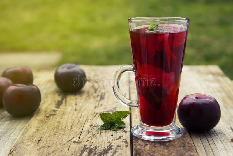 Chá vermelho erval e do fruto no copo de vidro e chá com ameixas Tabela de madeira textured rústica Copie o espaço imagens de stock royalty free