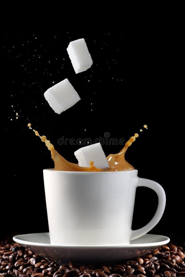 Chávena de café com espirro de cubos do açúcar fotografia de stock