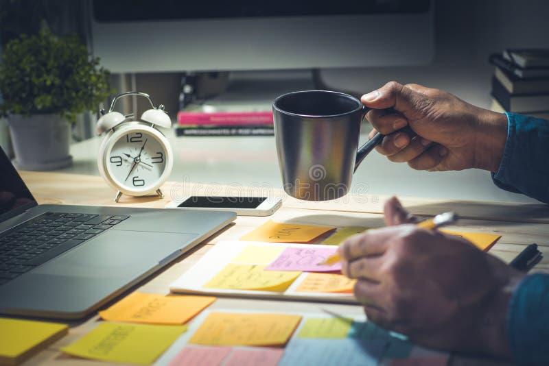 Chávena de café da terra arrendada do homem de negócios trabalho no conceito da noite imagem de stock royalty free