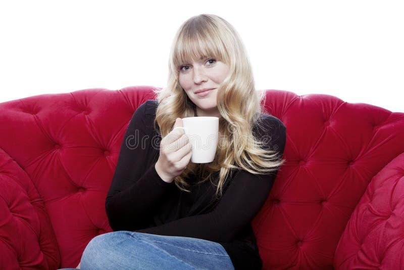 Chávena de café de cabelo loura nova da bebida da menina no sofá vermelho na parte dianteira fotografia de stock royalty free