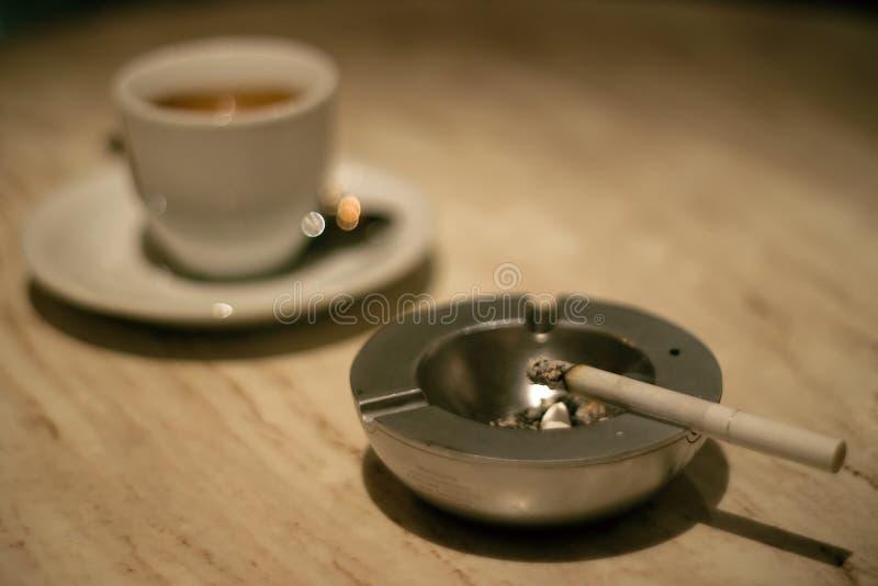 Chávena de café e cigarro no cinzeiro foto de stock