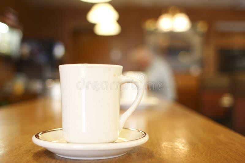 Chávena de café em um comensal imagem de stock
