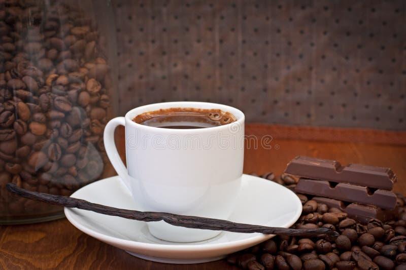 Chávena de café, feijão de baunilha e chocolate fotografia de stock