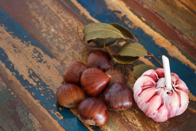 Châtaigne, ail et feuille de laurier sur la table en bois photos libres de droits