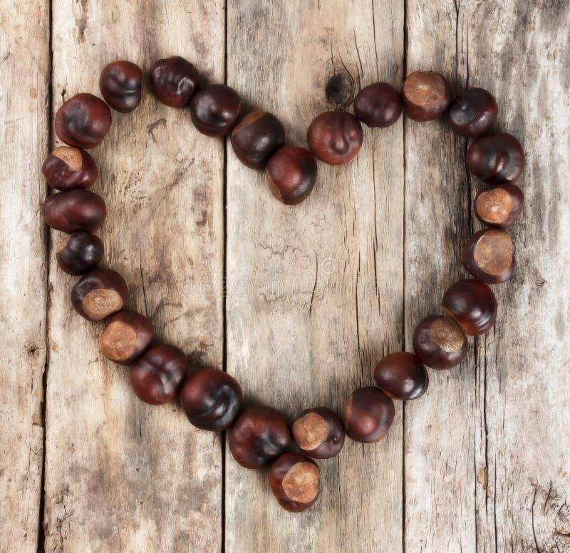 Châtaignes formant un coeur sur un fond en bois image stock