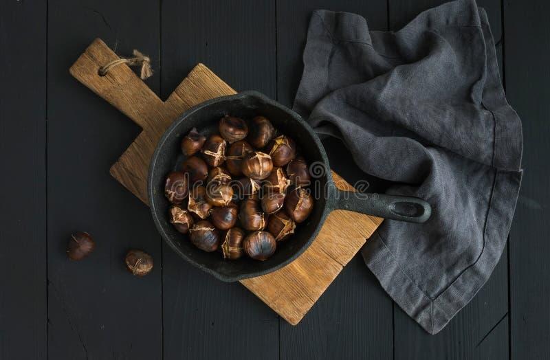 Châtaignes rôties dans la casserole de poêle de fer sur le conseil en bois rustique photographie stock