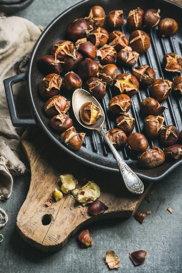 Châtaignes rôties en fonte grillant la casserole au-dessus du conseil en bois images libres de droits