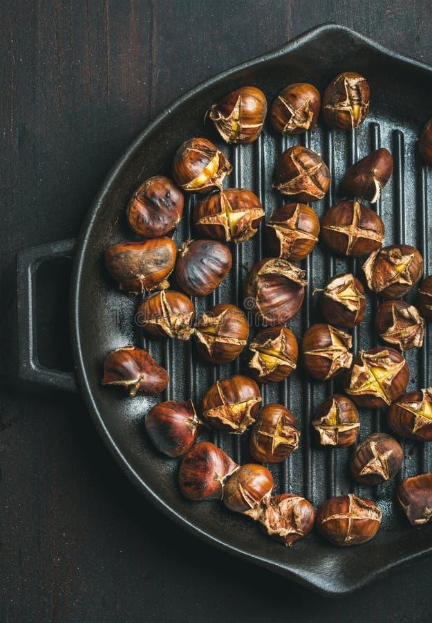 Châtaignes rôties en grillant la casserole au-dessus du fond en bois foncé images stock