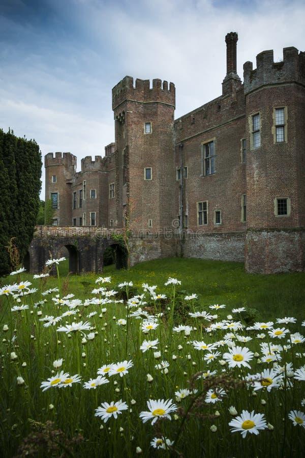 Château de Herstmonceux vu à travers ses raisons avec des marguerites s'élevant dans le premier plan images libres de droits