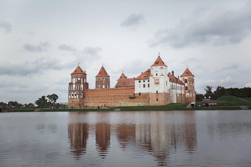 Château de MIR avec la réflexion dans l'eau du lac un jour nuageux photographie stock libre de droits