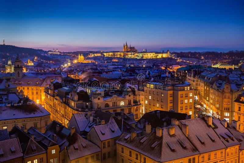 Château de Prague avec des dessus de toit de neige pendant le coucher du soleil en retard de Noël avec le ciel bleu photos stock