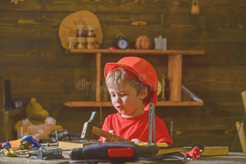 Chłopiec śpiewacka piosenka podczas gdy młotkujący gwóźdź w drewnianego blok Mały dzieciaka obsiadanie przy pracującym stołem w w obraz royalty free