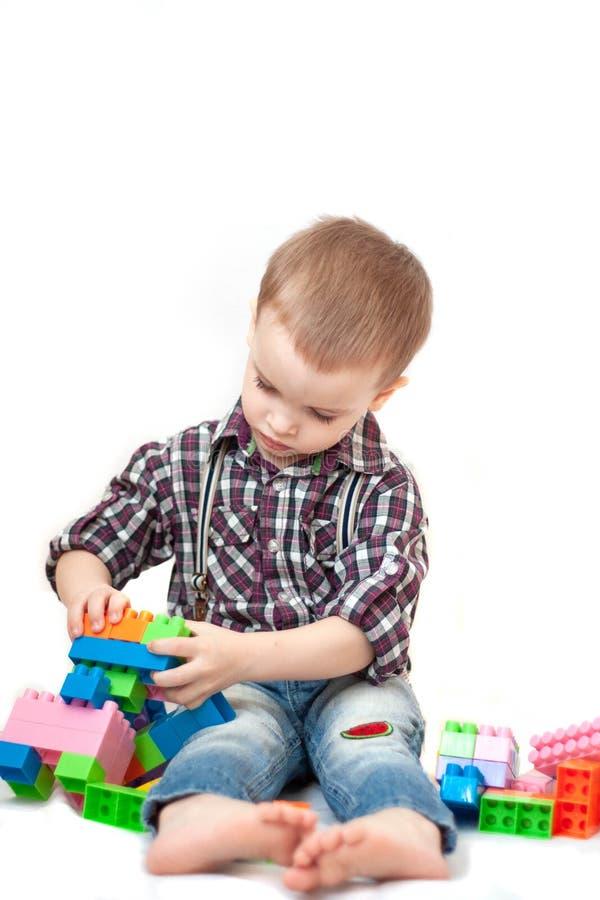 Chłopiec bawić się z blok zabawkami odizolowywać na białym tle obraz stock