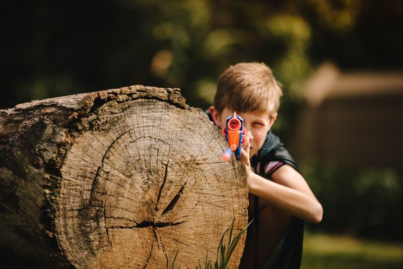 Chłopiec bawić się z zabawka pistoletem w boisku zdjęcia royalty free