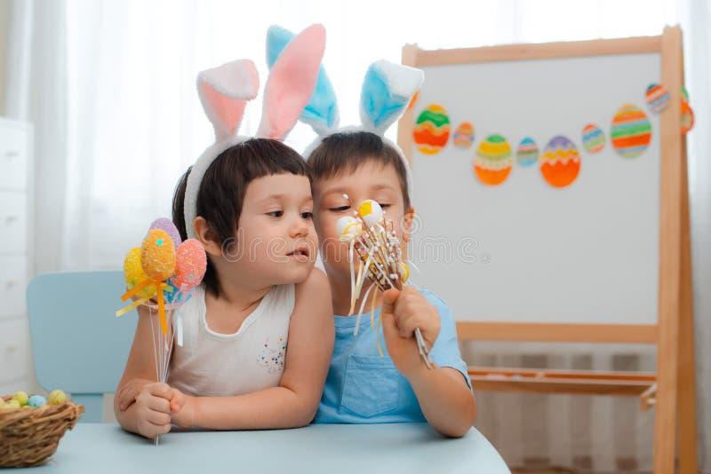 Chłopiec i dziewczyna w królików ucho bawić się z Wielkanocnymi jajkami Dzieciaki świętuje wielkanoc fotografia royalty free