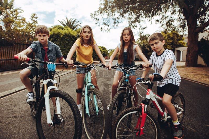 Chłopiec i dziewczyny na bicyklach w ulicie obraz royalty free