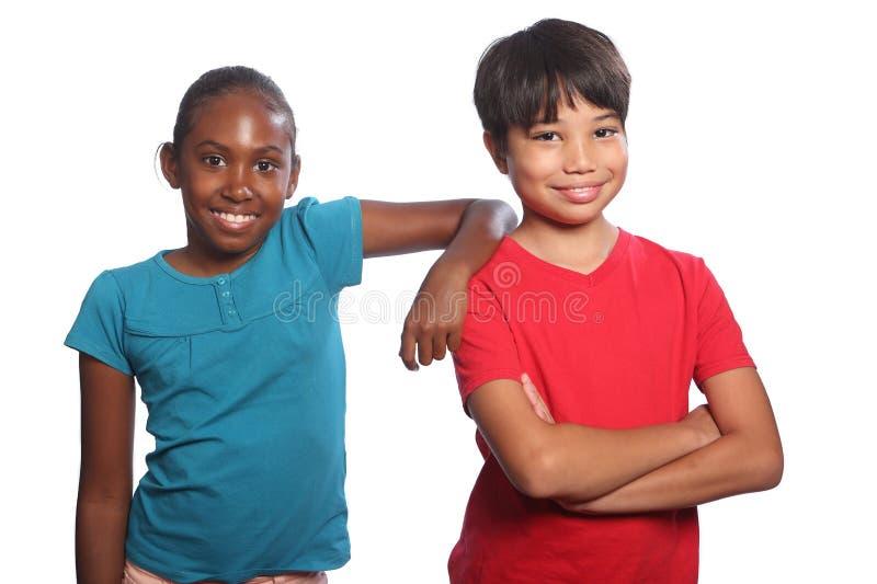 Chłopiec i dziewczyny wielorasowej pary szkoły szczęśliwi dzieciaki zdjęcia royalty free