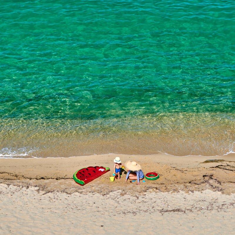Chłopiec i jego matka na plaży z nadmuchiwanym pławikiem fotografia royalty free