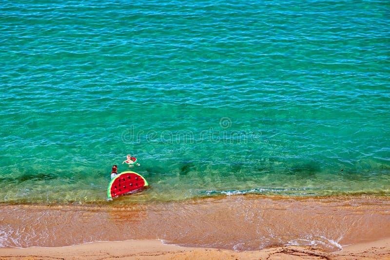 Chłopiec i jego matka na plaży z nadmuchiwanym pławikiem obrazy stock