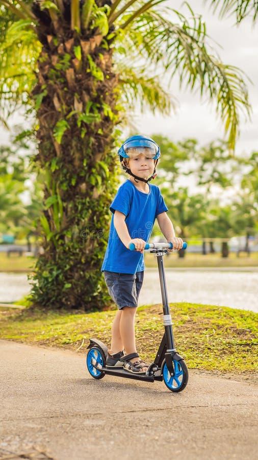 Chłopiec jeździeckie hulajnogi, plenerowe w parku, lato Dzieciaki są szczęśliwi bawić się outdoors PIONOWO format dla Instagram fotografia stock
