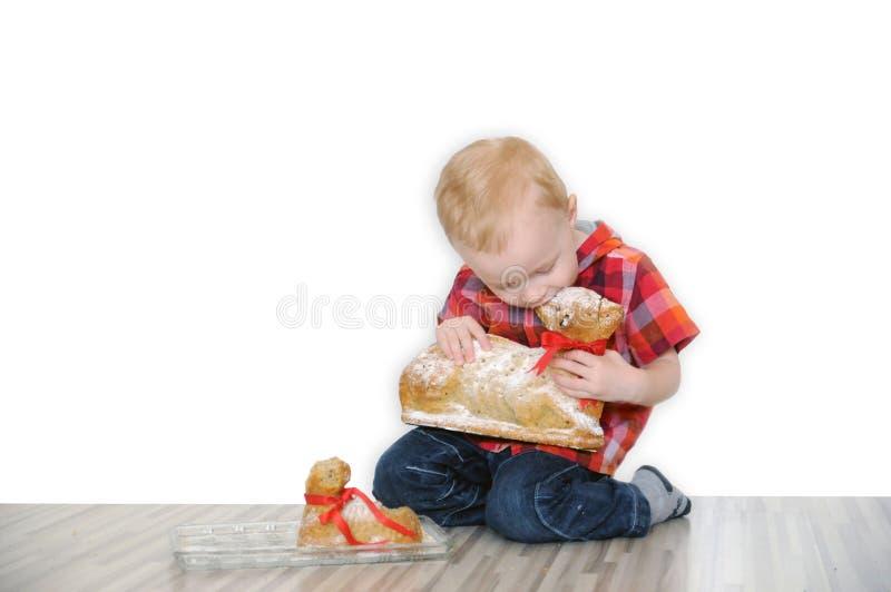 Chłopiec je słodkość w formie Wielkanocnego baranka obrazy royalty free