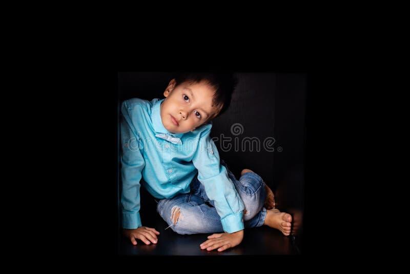Chłopiec jest ubranym błękitną koszula z krawatem siedzi w czarnym pudełku Chował lub fantasizes, dzieci lubi wspinać się w pudeł zdjęcie royalty free
