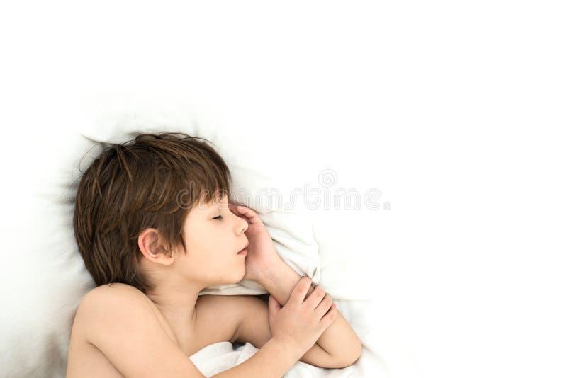 Chłopiec kłama w łóżku na białych bedclothes wśliznąć dziecka zdjęcia stock