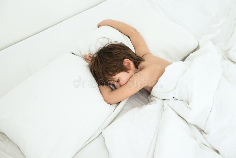 Chłopiec kłama w łóżku na białych bedclothes wśliznąć dziecka fotografia stock