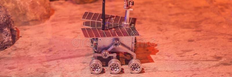 Chłopiec kontroluje zabawkarskiego włóczęgi na Mars Lot Mars pojęcia sztandar, DŁUGI format zdjęcie royalty free