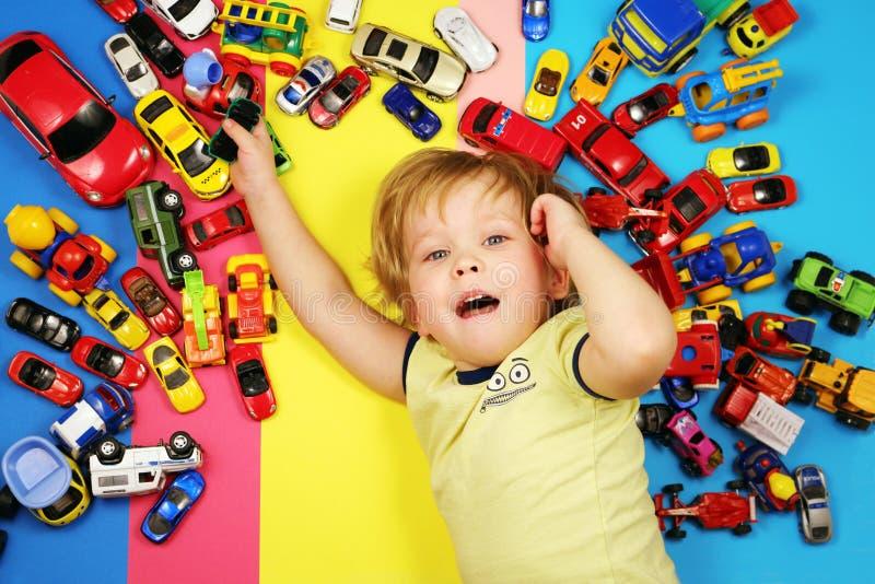 Chłopiec na stubarwnym tle otaczającym zabawkarskimi samochodami obraz royalty free