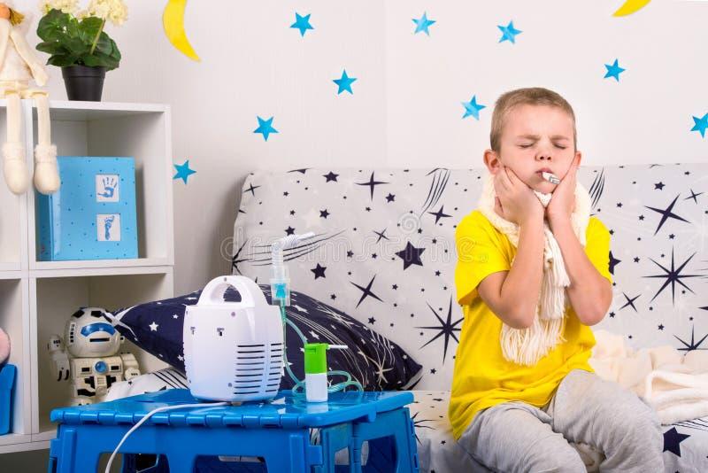Chłopiec odczucia bolą w gardle, miary temperatura Dziecko robi inhalacyjnemu nebulizer obraz stock