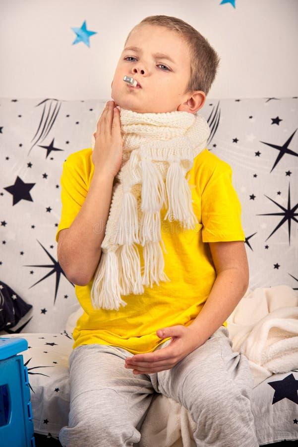 Chłopiec odczucia bolą w gardle, miary temperatura zdjęcie royalty free